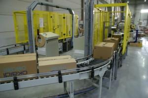 In een geïntegreerd dozensluitstation worden de orderdozen automatisch getaped én omsnoerd