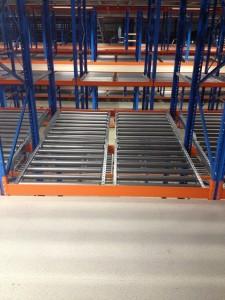 Een entresolvloer van Stow Nederland die is opgehangen tussen twee palletstellingen met doorrolkanalen